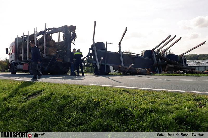 Boomstam valt van gekanteld vrachtwagen aanhanger op dak auto [+foto's]