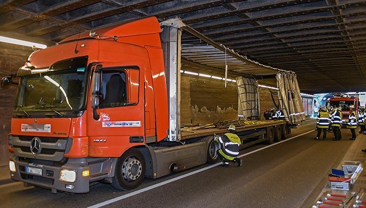 Vrachtwagenchauffeur schat vrachtwagen te laag in en komt klem te zitten onder spoorbrug [+foto's]