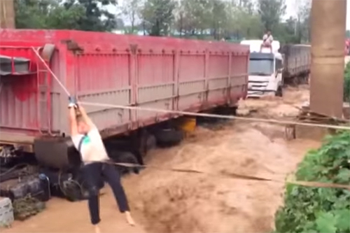 Vrachtwagens meegesleurd tijdens overstromingen in China [+video's]