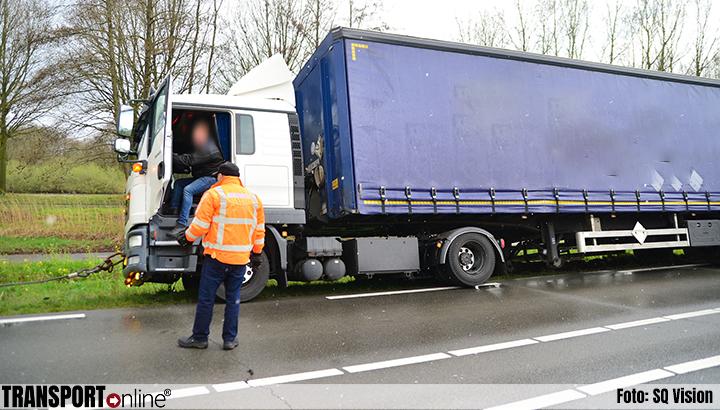 Vrachtwagenchauffeur wijkt uit voor politiewagen en komt vast te zitten in berm [+foto]